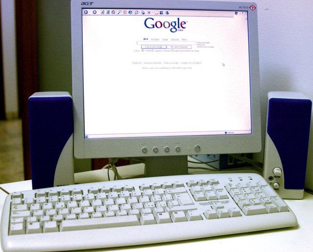 monitor, otevřená stránka google, vedle modrobílé reproduktory a bílá klávesnice